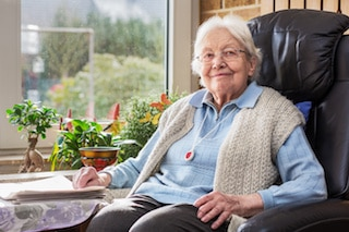 elder care connections provided senior referral services to happy elderly woman in lounge chair