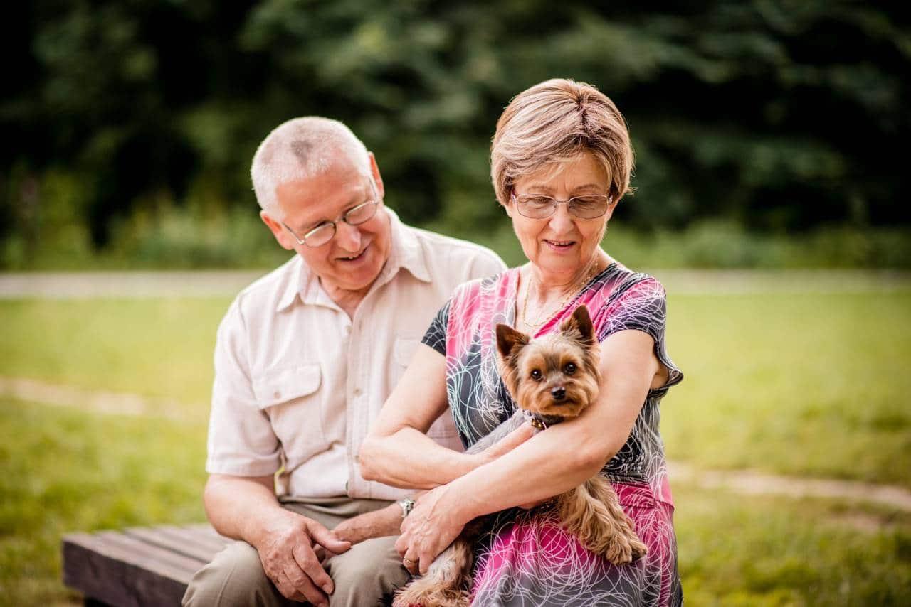 happy couple with dog enjoying senior housing and independent living