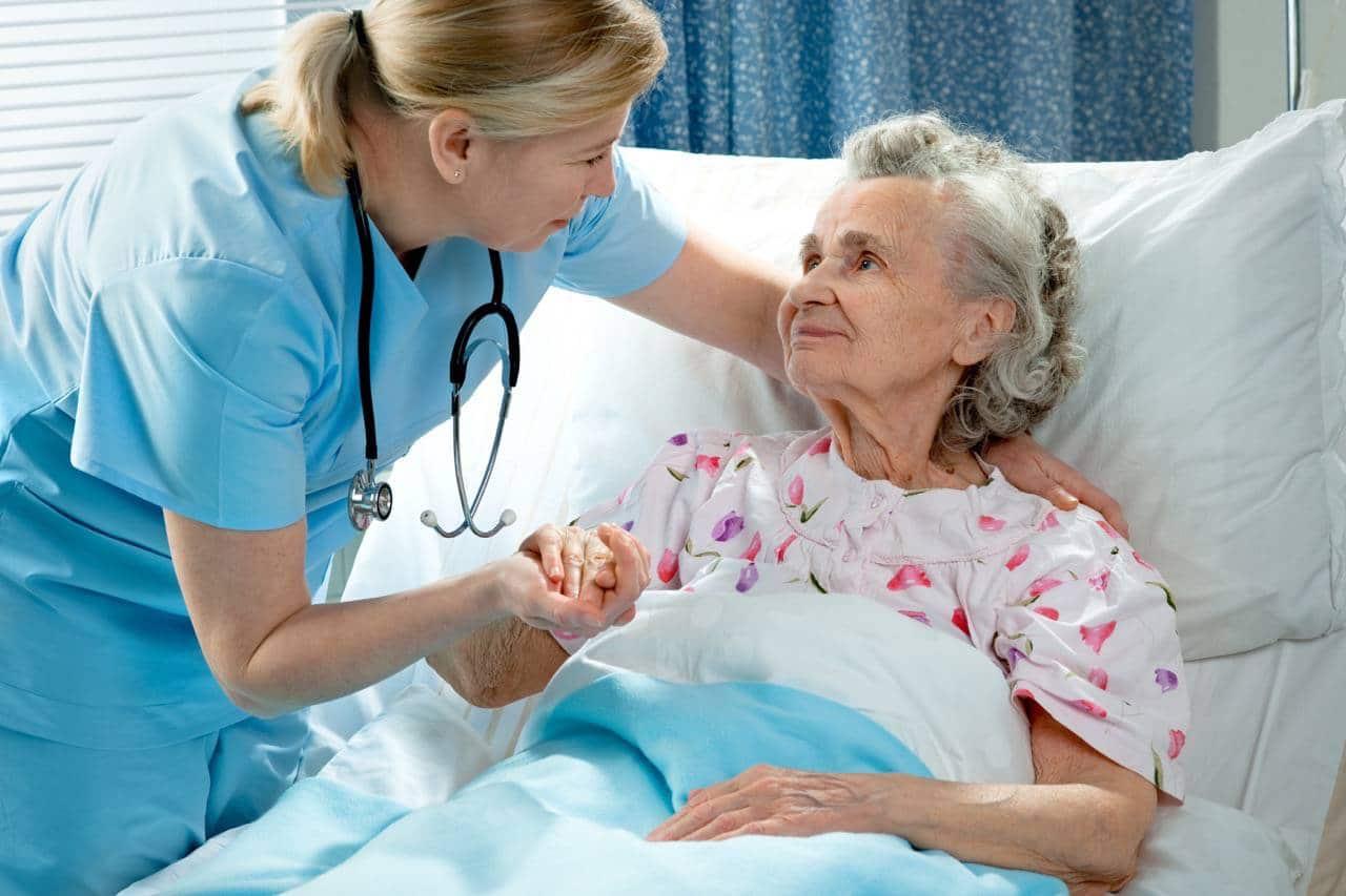 senior care facilities nurse assisting women in bed in senior housing
