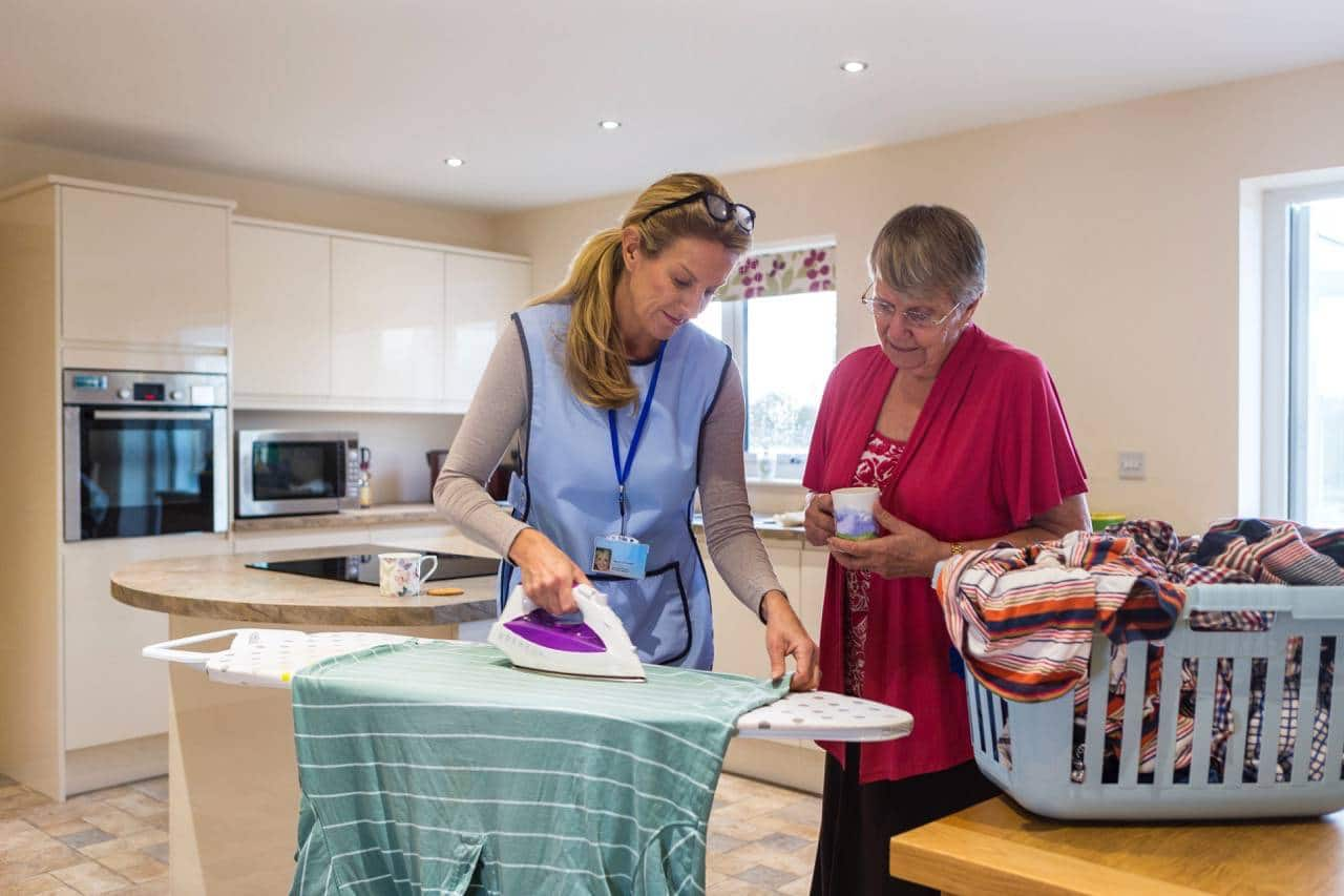 senior housing staff helping with ironing clothes